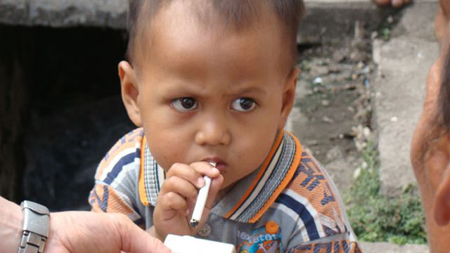 "PHOTO: Two-year-old Chairul likes to light up right after a nap. His grandfather says he allows Chairul to smoke because it tastes good, ""like bread with chocolate."""