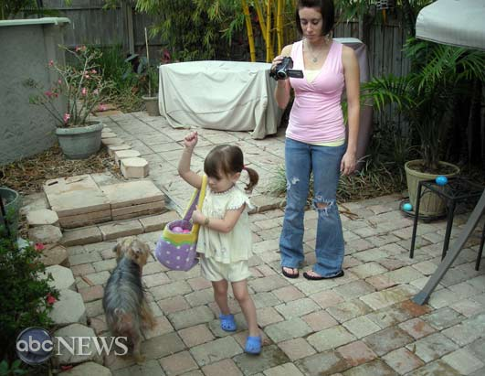 Caylee collecting candy-filled Easter eggs in 2008. Her mother, Casey, is seen filming her.