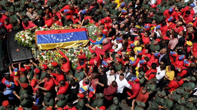 People walk alongside the flag-draped coffin containing the body of Venezuela's late President Hugo Chavez from the hospital where he died, to a military academy where it will remain until his funeral in Caracas, Venezuela, Wednesday, March 6, 2013.