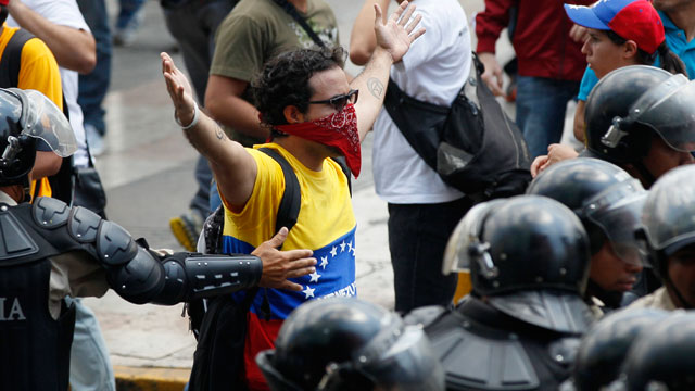 Anti-riot police try to stop an opposition student protester from advancing toward supporters of Venezuelas late President Hugo Chavez in Caracas, Venezuela, Thursday, March 21, 2013.