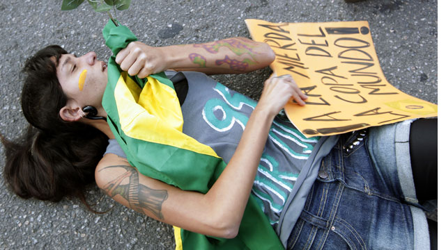"PHOTO: A protester lies on the ground in front of a police line in Rio de Janeiro, Brazil, Sunday, June 16, 2013. Her sign reads ""To hell with the World Cup."" Plans to increase bus fares sparked a wave of protests in Brazil last week."