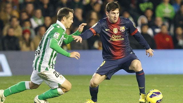 PHOTO: Barcelona's Lionel Messi from Argentina, right, and Betis' Nacho Perez, left, vie for the ball during their La Liga soccer match at the Benito Villamarin stadium, in Seville, Spain on Sunday, Dec. 9, 2012