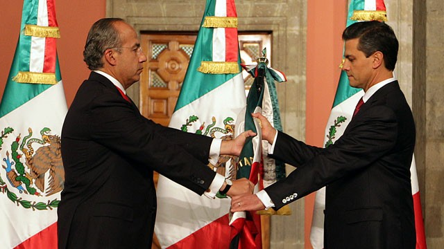 PHOTO: Mexico's outgoing president, Felipe Calderon, left, gives a Mexican flag to president-elect Enrique Pena Nieto during the official transfer of command ceremony at the National Palace in Mexico City, Saturday Dec. 1, 2012.