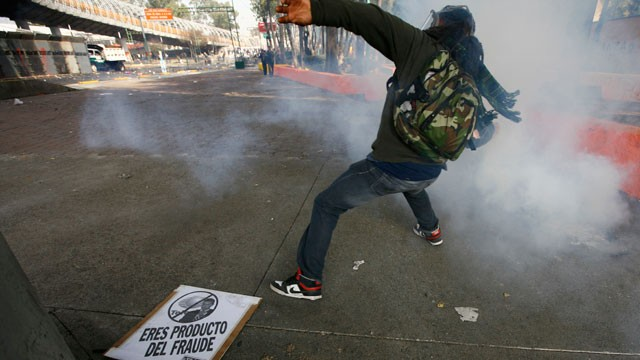 PHOTO: A demonstrator throws a stone to police during protests against new Mexican President Enrique Pena Nieto's rule, outside the National Congress, in Mexico City, Saturday, Dec. 1, 2012.