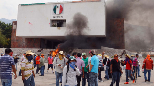 PHOTO: Protesting teachers stand outside the regional offices of the Revolutionary Institutional Party, PRI, after they attacked the building causing significant damage in Chilpancingo, Mexico, Wednesday, April 24, 2013.