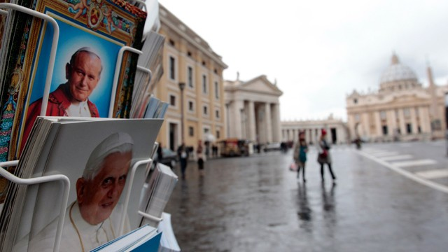 PHOTO: Postcards of Pope Benedict XVI, bottom, and late Pope John Paul II, are displayed outside a kiosk with St. Peter's Basilica in the background, at the Vatican, Monday, Feb. 11, 2013.