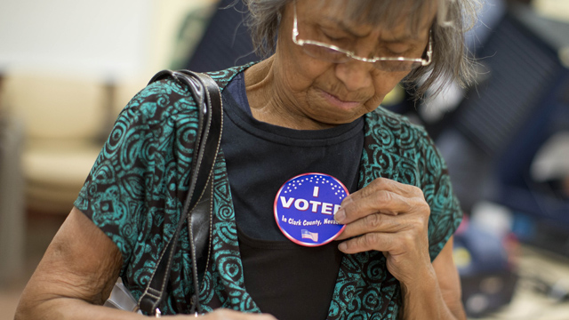 PHOTO: Aida Castillo places a sticker on her blouse indicating that she had voted during the early voting period, Saturday, Oct. 20, 2012, in Las Vegas.