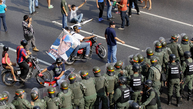 PHOTO: Opposition supporters on motorcycles confront riot police on a highway in the Altamira neighborhood of Caracas, Venezuela, Monday, April 15, 2013.