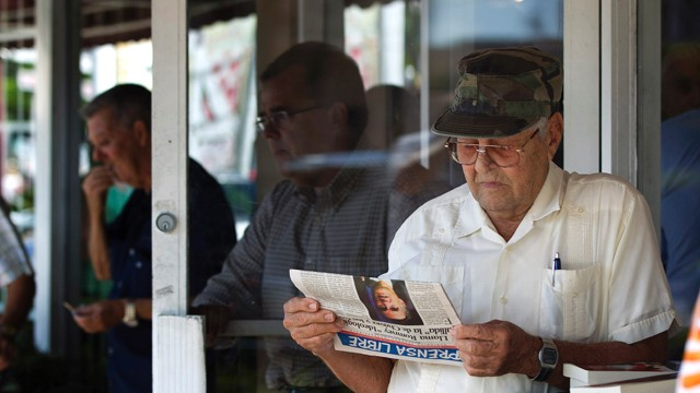PHOTO: Nino Diaz reads a Spanish language newspaper at a Cuban cafe in Miami's Little Havana section.