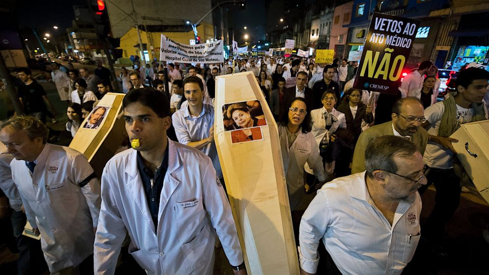 PHOTO: Doctors hold a coffin with the picture of Brazilian President Dilma Rousseff as they protest against the hiring of foreign medical doctors for Brazils health care system, in Sao Paulo, on July 16, 2013.