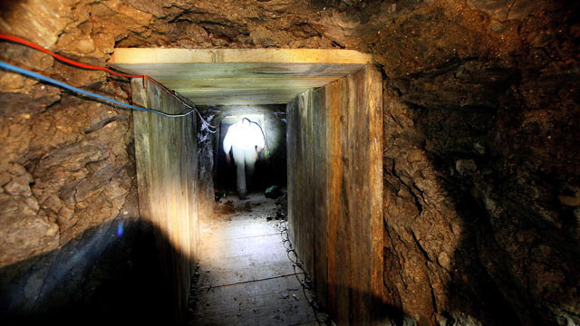 PHOTO: An investigator combs through a drug tunnel found in a wharehouse on November 30, 2011 in Otay Mesa, California.