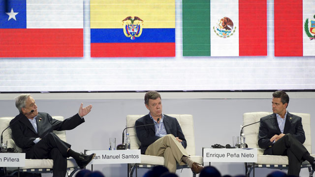PHOTO: Chiles President Sebastian Pinera (L) speaks next to Colombias President Juan Manuel Santos (C) and Mexicos President Enrique Pena Nieto during a meeting with businessmen at the Pacific Alliance presidential summit in Cali, Colombia, on May 23,