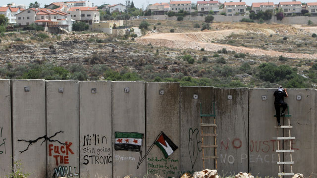 PHOTO: A palestinian protester climbs Israel's controversial West Bank barrier.