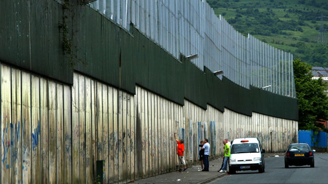 PHOTO: A visitor to Belfast, adds her own personal message to the Peace Wall.