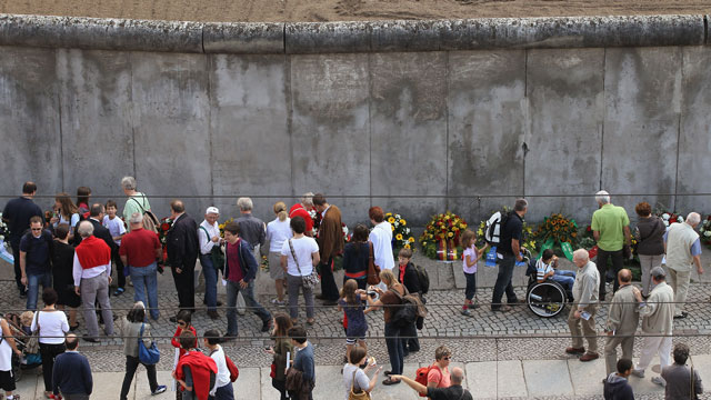 Visitors look at wreaths left at a still-standing portion of the Berlin Wall.
