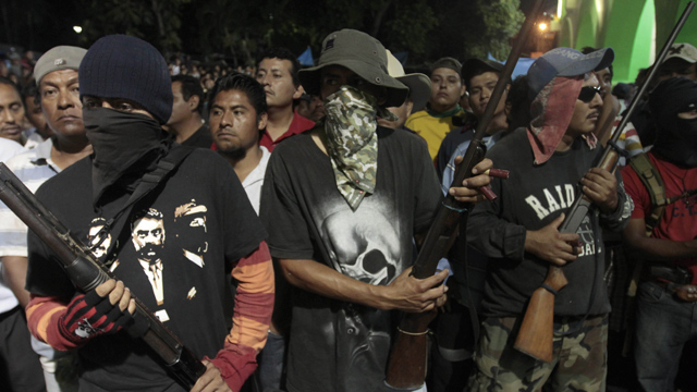 PHOTO: Hooded men stand guard while passing detainees to the Government of the State of Guerrero by the communitarian police at the central square of Ayutla de los Libres, on Febrary 8, 2013. On Tuesday, a final batch of 39 detainees was released.