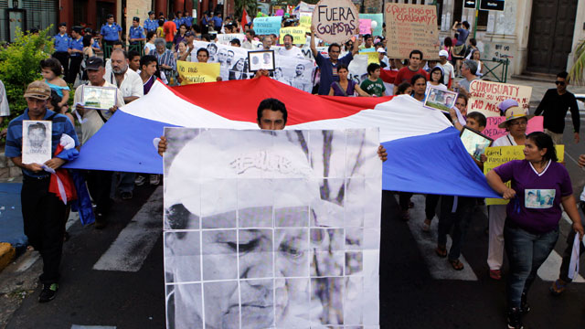PHOTO: Activists, one carrying a sign with an image of killed peasant leader Vidal Vega, march during a demonstration in Asuncion, Paraguay, Monday, Dec. 10, 2012. Demonstrators asked for clarification of the murder of Vega and the massacre of Curuguaty.