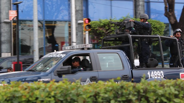 PHOTO:&nbsp;Mexican Federal police, with semi-automatic machine guns patrol Acapulco&acute;s main tourist avenue, the Avenida Costera.