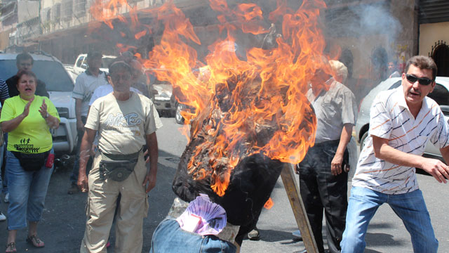 PHOTO: Watch out for the burning effigy! Residents of Caracas burned dummies of their most hated politicians on Sunday.