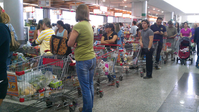 PHOTO:  Customers wait in long lines at the Excelsior Gamma supermarket in the neighborhood of Sebucan in Caracas, Venezuela.