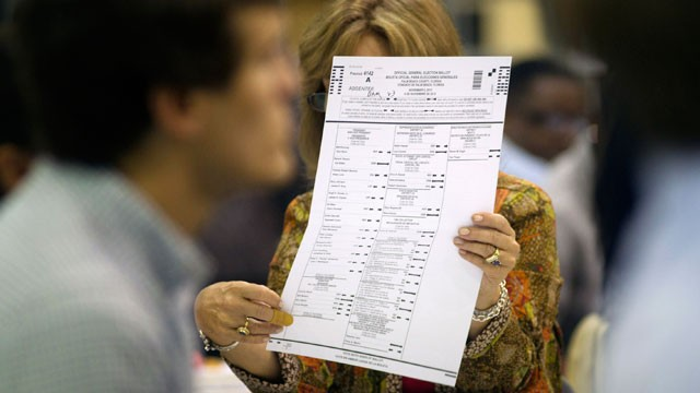 This Oct. 23, 2012 photo shows a county election worker checking an absentee ballot at the Post Beach county election board office in Riviera Beach, Fla. Because of a printing error, somewhere around 27,000 absentee ballots already cast by voters are bein