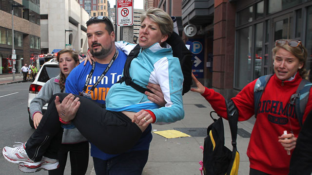PHOTO: In this Monday, April 15, 2013 photo, former New England Patriots player Joe Andruzzi carries a woman from the scene of two blasts at the finish line of the Boston Marathon on Exeter Street in Boston.