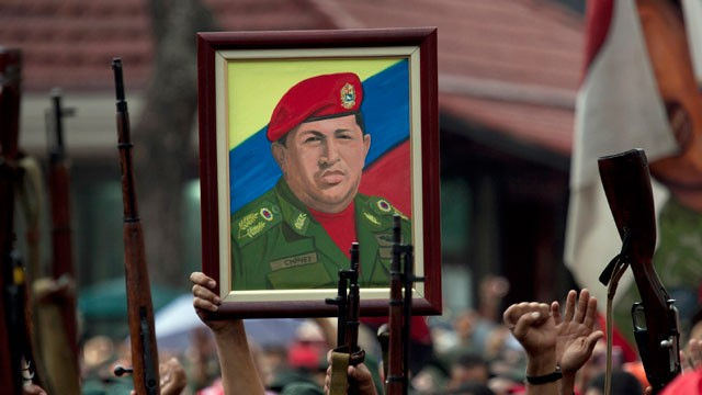 PHOTO: Members of the National Revolutionary Militia, also called Bolivarian militias, hold up their guns and a painting of Venezuela's President Hugo Chavez.