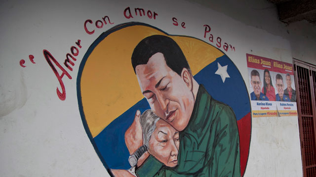 PHOTO: A heart-shaped mural shows an image of Venezuelas President Hugo Chavez hugging a woman in Caracas.
