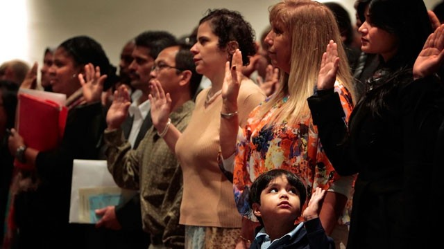 PHOTO:&nbsp;Solemnly raising his hand, Shamir Aijaz, 5, joins with the rest of the crowd as his mom Fariha Aijaz, right, to take the oath of citizenship Monday Dec. 10, 2012, in Germantown, Tn. during a special naturalization ceremony at Houson High School.