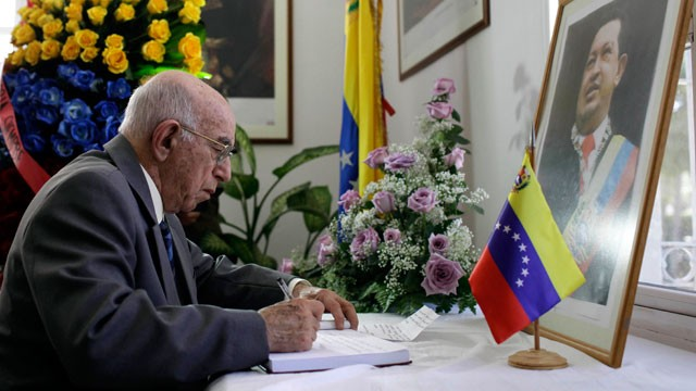 PHOTO: Cuba's Vice President of the Council of State, Jose Ramon Machado Ventura, writes in a book of condolence for Venezuela's late President Hugo Chavez
