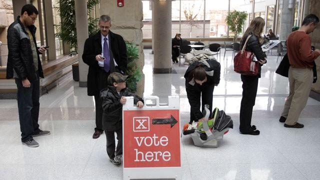 PHOTO: Cole Cryan, 4, leans on a sign directing voters while waiting with his mother, Monday, Nov. 5, 2012, at the Wood County Court House in Bowling Green, Ohio.