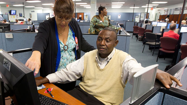 PHOTO: WorkForce One staffer Rose Capote-Marcus works with a client, Pen Osuji as he works on job applications.