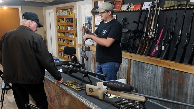 PHOTO:&nbsp;Clerk Lance McCoy, right, shows a variety of weapons Thursday, Dec. 20, 2012, including an AR-15 style semi-automatic at Kizer Guns and Ammo near Nacogdoches, Texas.