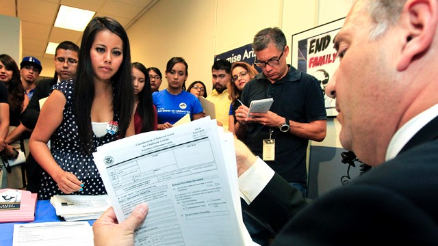 PHOTO: Young immigrants, including Gaby Perez, hand over paperwork to get guidance from immigration attorney Jose Penalosa for Obama's deferred action policy.