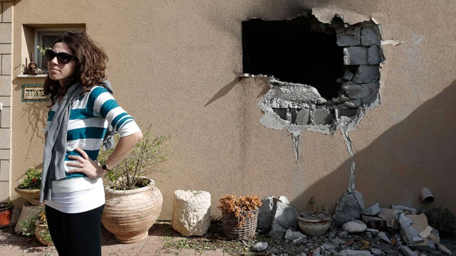 An Israeli woman stands outside a damaged house hit by a rocket fired from the Gaza Strip that hit a house near the Israel-Gaza border, Friday, Nov. 16, 2012.