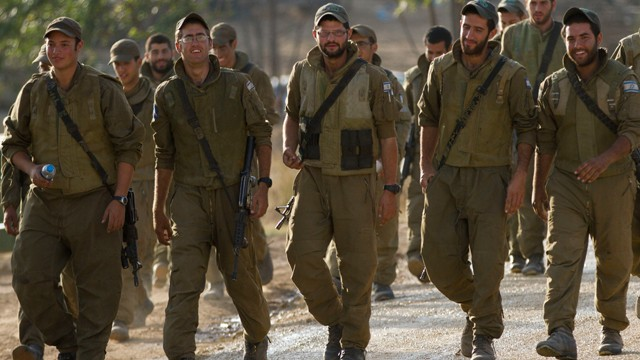 Israeli soldiers march in a gathering area near the Israel Gaza Strip border, in southern Israel, Sunday, Nov. 18, 2012.