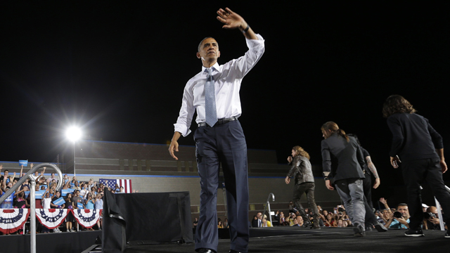 PHOTO: President Barack Obama waves to supporters as members of the Mexican Rock band Mana walk off stage during a campaign event.