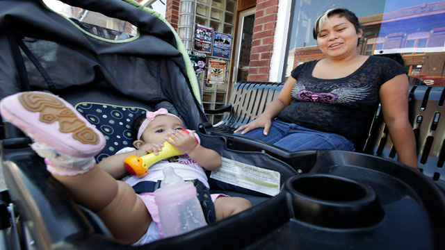 Erika Reyes sits with her seven-month-old daughter on Main Street, Wednesday, Aug. 22, 2012, in West Liberty, Iowa.