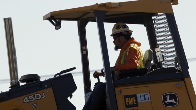 A worker runs a bulldozer on a light rail bridge construction project over the Willamette River in Portland, Ore., Friday, Oct. 5, 2012. Hispanics and blacks still suffer higher unemployment and underemployment.
