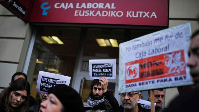 PHOTO: Citizens affected by bank mortgage and evictions protest in front a regional bank displaying banners reading, ''This Bank deceives, swindling and fire people of their house'', in Pamplona northern Spain on Tuesday, Dec. 18, 2012.