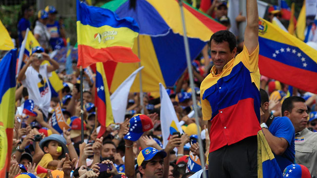The oppositions presidential candidate Henrique Capriles, top, gestures to supporters during a campaign rally in Caracas , Venezuela, Sunday, Sept. 30, 2012.