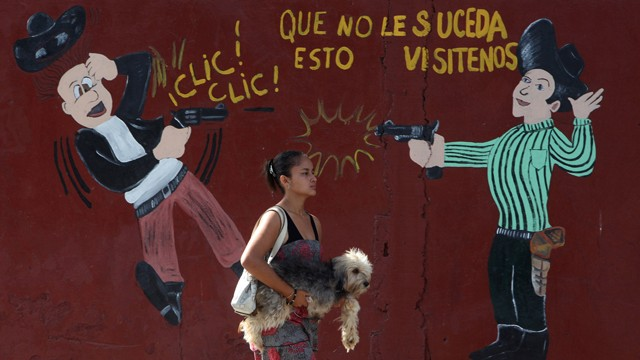 PHOTO:&nbsp;A woman carries her dog past an armory shop in San Pedro Sula, Honduras. Honduras has more homicides than any other country in the world with 91 per 100,000 people, the World Health Organization says.