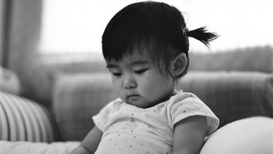 PHOTO: Baby with braids sitting on bed looking down