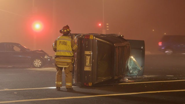 PHOTO:&nbsp;A Roseville Fire Department firefighter looks over an overturned vehicle after a collision at Blue Oaks Boulevard and Woodcreek Oaks Boulevard in Roseville, California on 11/26/2011