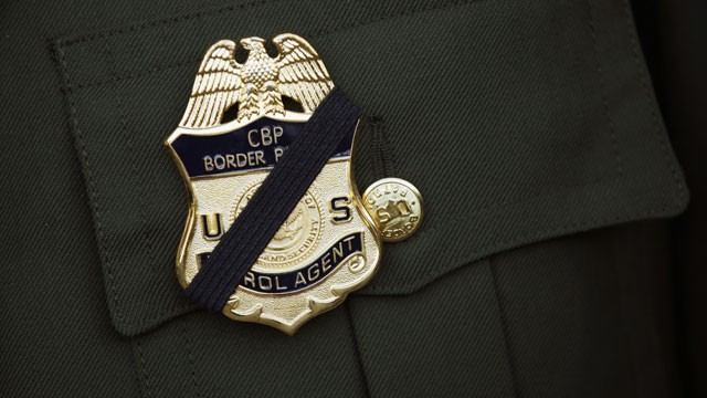 A U.S. Border Patrol agent wears a black band on his badge during a memorial service for slain comrade Brian Terry on January 21, 2011 in Tucson, Arizona. Terry was killed during a December 2010 shootout with suspected bandits near the U.S.-Mexico Border.