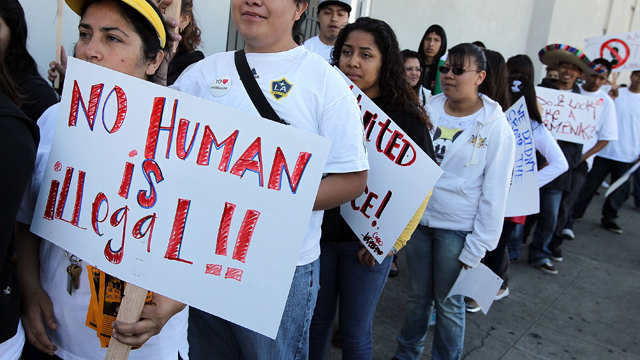 PHOTO: OAKLAND, CA - APRIL 30: People with the group 'Youth United For Justice' hold signs in protest of Arizona's immigration law.