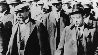 PHOTO: Italian anarchists Nicola Sacco (1891 - 1927) (R) and Bartholomeo Vanzetti (1888 - 1927) (L) walking in a crowd handcuffed after being accused of the murder of a paymaster and a guard in Braintree, Massachusetts.