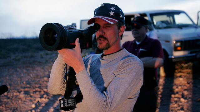 PHOTO: Chris Simcox, one of the organizers of the Minuteman Project, looks through an infrared scope trying to spot people moving towards the United States border April 2, 2005 near Naco, Arizona.