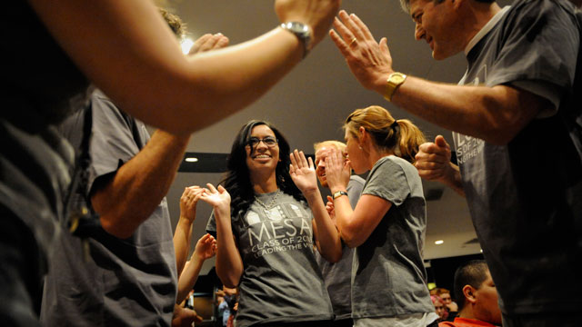 PHOTO: Lorena Olivas, a senior at Mapleton Expeditionary School of the Arts in Thorton, Colorado, walks through a tunnel of teachers and staff as part of a weekly college acceptance ritual on May 14, 2008.