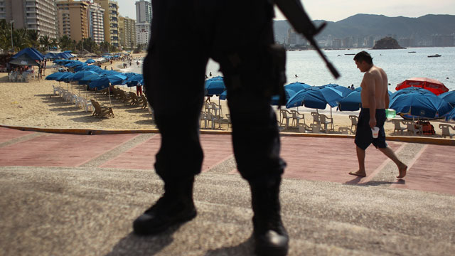 PHOTO:  A Mexican federal policeman stands guard near the beach on March 4, 2012 in Acapulco, Mexico.